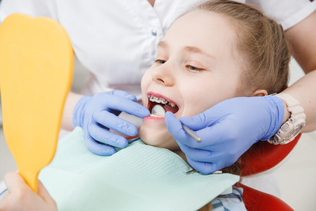 Girl having her teeth examined by a dentist