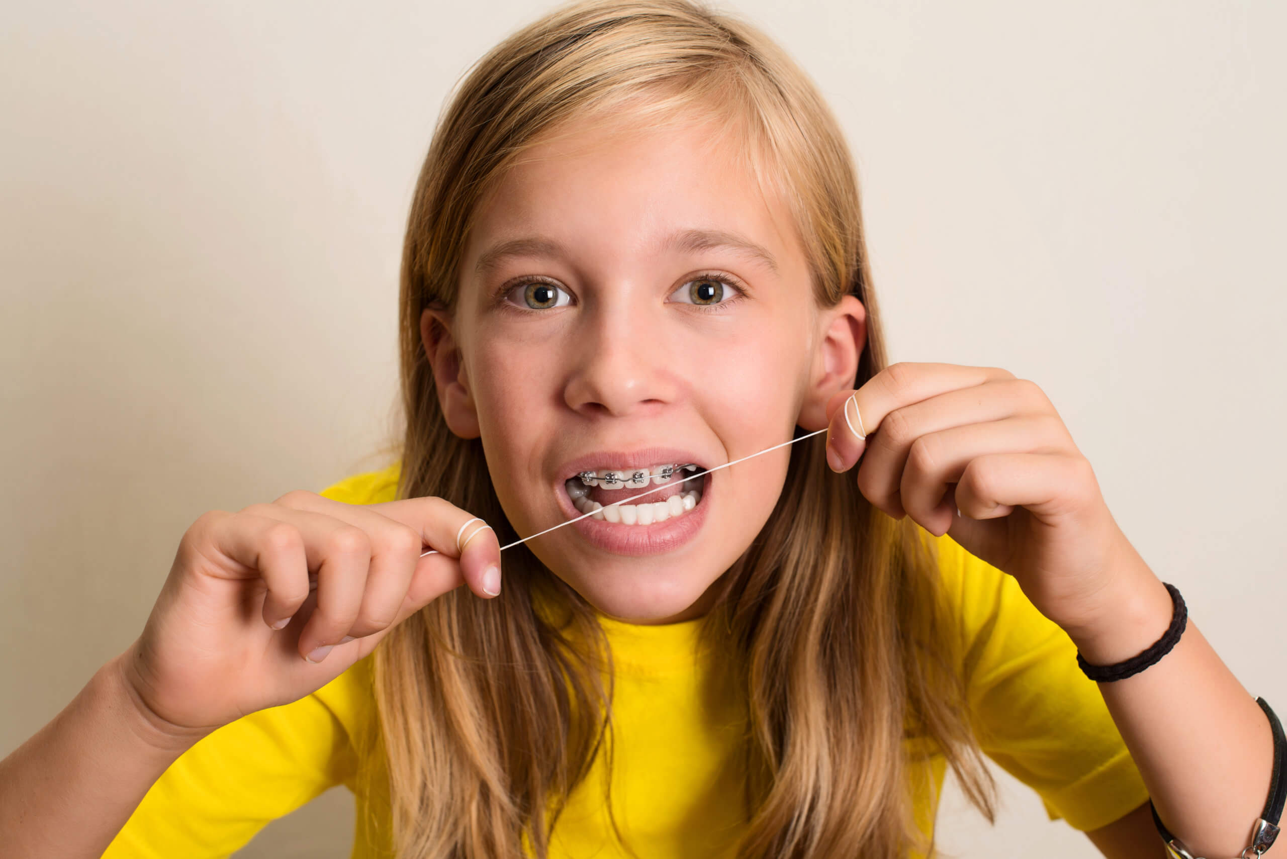 Pediatric smiles - patient with braces flossing